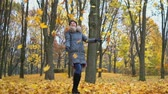 despreocupado : A woman tosses leaves in an autumn park Vídeos