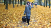 A woman is walking and talking on her mobile phone, carrying a suitcase. Stock Footage