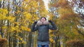 A woman is dancing in an autumn park