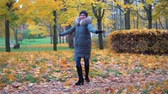 vlasy : A woman is dancing in an autumn park