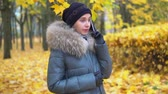 Woman emotionally talking on the phone in an autumn park