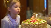 Little girl blowing out candles on a cake Stock Footage