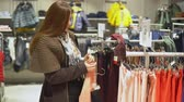 şehir merkezinde : A woman chooses childrens clothes in a store. Stok Video