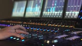 A man works in a recording studio on a mixing console. Hands close up Стоковые видеозаписи
