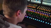 A man works in a recording studio on a mixing console. Стоковые видеозаписи