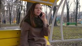 confident : Beautiful woman relaxing on a swing and holding smart phone. Selective focus.