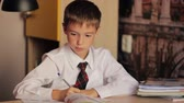 first class : Little boy schoolboy 8 years closeup in a white shirt and tie is sitting at a table and writes in  a notebook pen Stock Footage