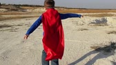 field : superhero boy runs through the mountains and trying to fly