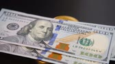 international economy : Golden bitcoins on hundred-dollar bills. Virtual money replacement paper