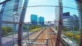 выстрел : Train traveling through Tokyo. Shot from moving vehicle a bridge above. Стоковые видеозаписи