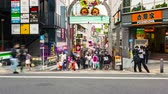 walk : TOKYO - CIRCA JUNE 2015: People walk and shop along the Takeshita Street in Harajuku, Tokyo, Japan. Takeshita street is a pedestrian-only street lined with cafes and boutiques famous for its fashion trends.