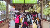 japão : TOKYO - CIRCA JUNE 2015: School girls with brightly colored backpacks enter the Yamanote line at Harajuku Station, Tokyo, Japan. Vídeos