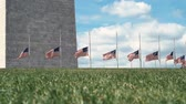 yönetme : American flags blowing in the wind at the base of the Washington Monument Stok Video