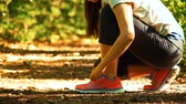 tkanička : Female runner lacing her sneakers on a forest trail