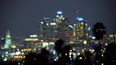 escuro : Downtown Los Angeles at night with palm trees in the foreground