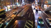 Traffic passes through a busy intersection in Osaka, Japan on a rainy night Stock Footage