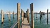 Girl is standing on the boats wharf, Venice, Italy