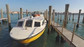 benátský : Yellow motor boat moored at boats wharf, Venice, Italy