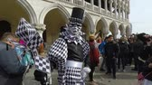 manto : Carnival of Venice, Italy – February 2018. Costumed actor walk through St Marks square. Actor with black and white mask pose, random tourists. Carnevale di Venezia
