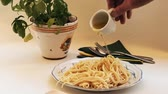 Spaghetti - freshly cooked and delicious, are doused with olive oil and seasoned. Filmati Stock