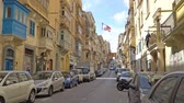 VALLETTA - MALTA, April, 2018: Tourists Walking along the medieval streets of Valletta, Malta.