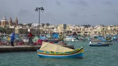 máltai : Marsachlokk - MALTA, April, 2018: Colorful Maltese boats in the harbor in Malta in the fishing village of Marsachlokk. Stock mozgókép