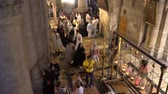 gyertyák : Jerusalem, Israel - November 2019: Holy Sepulcher Church in Jerusalem. The Church is the most sacred places for all Christians people in the world. Stock mozgókép