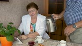 tea : An adult woman using a tablet, drinking tea at the table. Stock Footage
