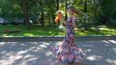dress : Beautiful young woman is dancing in a park with a bouquet of flowers.
