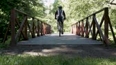 aerodynamics : A man is driving along a bridge in a park, on a bicycle. In summer time.