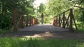 tepelik : A man is riding a bicycle across the bridge in the park. slow motion