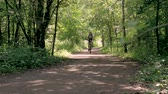 fixní : A man is training in the park. He rides a bicycle on a summer day, on special tracks. Dostupné videozáznamy