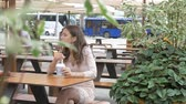 мороженое : Someone is watching a girl who is eating ice cream in a cafe on the street.