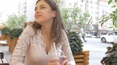 koni : Young beautiful brunette drinks a summer cocktail while sitting at a table in a street cafe. She is happy