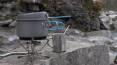 konvice na čaj : Close-up of a gas burner on which a kettle stands. It boils food. On the bank of a mountain river.