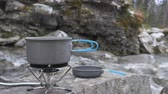 konvice : Close-up of a gas burner on which a kettle stands. It boils food. On the bank of a mountain river.