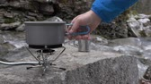пылающий : On a portable gas burner man puts a pot of water to cook dinner Close-up. On the bank of a mountain river. Стоковые видеозаписи