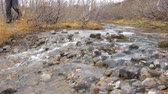 steppe : Tourist with a backpack goes through a mountain stream. View from the bottom. Stock Footage