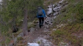 alpinista : Traveler with a backpack climbs up the mountain path. He explores new routes for himself. Active travel and healthy life.