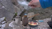 tea pot : On a portable gas burner there is a kettle. Coffee is thrown into it. Picnic near the mountain river. Close-up Stock Footage