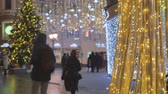 мигать : Silhouettes of people walking on the streets decorated for the holiday. On the background of Christmas lights. Out of focus.