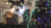 украшать : Urashennaya Christmas tree, close-up. In the background out of focus people in the store choose gifts. Festive atmosphere. Стоковые видеозаписи