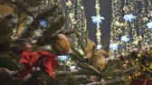csecsebecse : Christmas toys hanging on the branches of spruce. Festive decoration of the city. Out of focus festive lights.