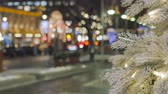 cam : Urashennaya Christmas tree, close-up. In the background out of focus people are walking. Festive atmosphere.