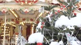 украшать : Christmas fir tree with toys close-up. Decoration of the city for the holiday. In the background out of focus turns the carousel, on which the children ride. Festive atmosphere.