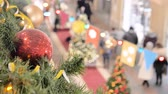 gratitude : Festive atmosphere in the mall. In the foreground a new year red ball. Not in focus people walk and buy gifts. Stock Footage