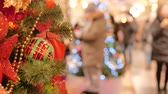 отраженный : Festive atmosphere in the mall. In the foreground Christmas fir. Not in focus people walk and buy gifts.