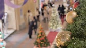 reflected : Festive atmosphere in the mall. In the foreground a new year ball. Not in focus people walk and buy gifts.