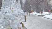 рамка : Festive atmosphere on the streets of the city. Christmas toys hanging on the tree. People are walking in the background.
