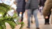 gratidão : Festive atmosphere in the mall. In the foreground Christmas fir. Not in focus people walk and buy gifts.